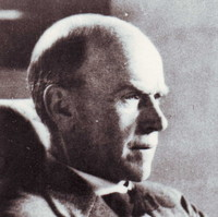 Image: A photographic head-and-shoulders portrait of a balding, middle-aged man in profile. He is wearing a mid-twentieth century suit and reading a document