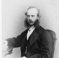 Image: Black and white portrait of a partially balding man with long mutton chops and a moustache sitting in a chair. He is wearing a shirt and suit jacket