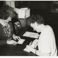 Image: two smiling caucasian women writing at a main desk in library