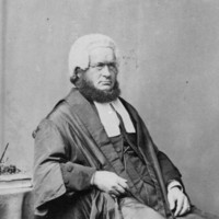 Image: Black and white portrait of a man, with the chin curtain beard popular at the time. He is seated and wearing his wig and gown.