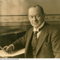 Image: portrait of a man in suit holding a card