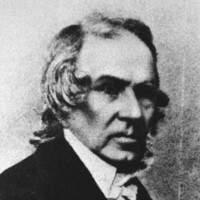 Image: A head-and-shoulders portrait of a middle-aged Caucasian man in mid-nineteenth century clerical attire. He is clean-shaven and has slightly long, shaggy greying hair