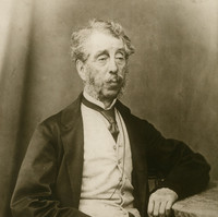 Image: Black and white portrait of a man with grey hair, mutton chops and a moustache. He is wearing a suit jacket, vest, shirt and tie.