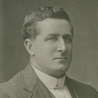 Image: Photographic portrait of a man in a suit jacket, vest and shirt.