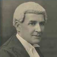Image: A man in a barrister wig and gown poses for a photograph. He is seated in a chair with his right profile facing the camera