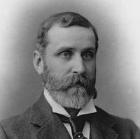 Image: A photographic head-and-shoulders portrait of a bearded, middle-aged man wearing a suit and tie