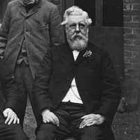 Image: Three elderly Caucasian men in late Victorian-era attire pose for a photograph outside a bluestone building. Two are seated while another stands.