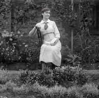 Image: A woman holding a book sits in a garden with several flowering and other plants