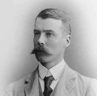Image: A photographic head-and-shoulders portrait of a young Caucasian man wearing a light-coloured, late-Victorian era suit and sporting a very large handlebar moustache