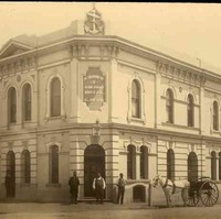 Image: sepia shot of building facade, with three men at the entrance, one by the side, and a horse-drawn carriage