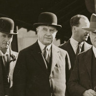 Image: A group of middle-aged Caucasian men dressed in early twentieth century suits and fedora hats stand in front of a brick building. A late-1920s model car is parked immediately behind the group