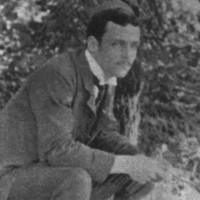 Image: black and white photograph of a man sitting in garden