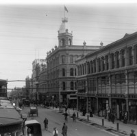 Image: black and white photo of street lined with three and four storey buildings