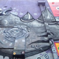 Image: zoom on blue and purple mural of rhinoceros' face, positioned on a brick wall