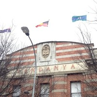 Image: top storey of red brick three-storey building, with three flags flying
