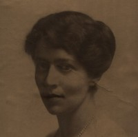 Image: A photographic head-and-shoulders portrait of a young Caucasian woman dressed in early twentieth century attire. She has dark hair and eyes and is wearing a pearl necklace and light cardigan sweater