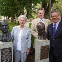 Image: Three people standing with two bronze busts