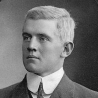 Image: A photographic head-and-shoulders portrait of a young Caucasian man wearing an early Edwardian suit. He is clean shaven and has light-coloured hair and eyes