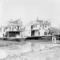 Image: Black and white photograph of two paddlesteamers anchored next to each other on a river. The paddlesteamer on the left is flying the Union Jack