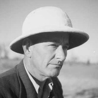 Image: A photographic head-and-shoulders portrait of a middle-aged man wearing a suit-jacket, open-necked shirt and pith helmet