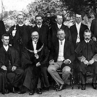 Image: A group of men in Edwardian attire pose for a photograph. One of the men is wearing a large mayoral collar