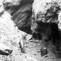 Image: A man stands at the bottom of a large crevasse. Next to the man is a wheeled bin, as well as partial timber structure