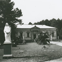 Image: statue of woman in front of tree and Greek Revival building