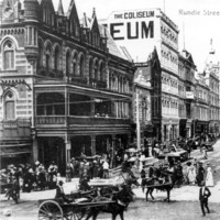 Image: Bustling street with ornate building and balcony