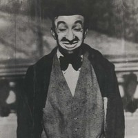 :Image Man in suit and hat poses and pulls silly face for the camera