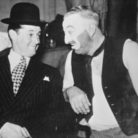 Image:Smiling man in suit and hat next to man in make-up and dirty vest