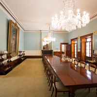 Image: A large room containing a long table with chairs. Two large portraits and a mirror hang on the walls