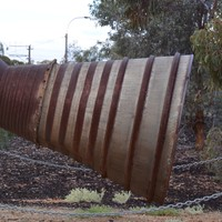 Image: The rusted exhaust section of a rocket mounted on a pedestal near a cluster of gum trees