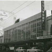 Image: a large 1950s era building with huge windows surrounded by much older buildings