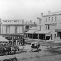 "Image:  A three horse team and laden wagon is standing on a dirt street near an intersection. In the centre of the view, a man on a scaffold is engaged in building work. The building on the near side of the intersection has a sign reading ""The Bee Hive"""