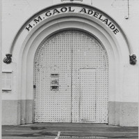 "Image: a large metal arched door with a sign reading: ""H.M. Gaol Adelaide"""