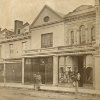 Image: A man and a boy in 1870s clothing stand outside a row of two storey terraced shops. The man is leaning on a post and the boy stands behind him.
