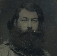 Image: a head and shoulders portrait of a man with long dark hair and a very thick long black beard. He is wearing a casual 1850s era shirt.