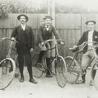 Image: three cyclists in hats pose with their bicycles