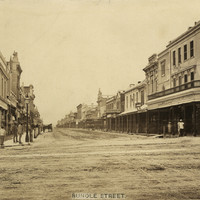 Image: a wide dirt city street, lined with shops, with a single horse drawn vehicle parked on the left of the street. Men are posing for the photograph on both sides of the road outside of shops.