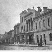 Image: a city street lined with two and three storey buildings. In the foreground is a corner hotel with patrons standing outside.