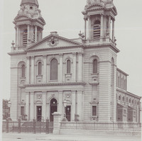 Image: A large church with twin spires, clerestory windows, and wide steps leading to a front door flanked by six decorative columns, three on either side, which are repeated on a second storey and topped by a pediment.