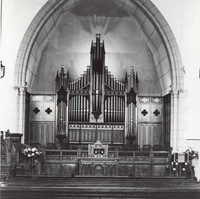 Image: a large church organ under a pointed stone arch
