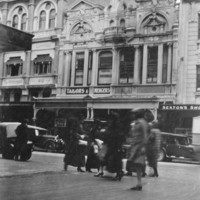 Image: a group of women in 1920s era coats cross an intersection. On the other side of the road are ornate three and four storey buildings with shops including a tailor and Balfours Bakery.