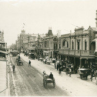 Image: a dirt street, lined with two and three storey stone buildings and busy with horse drawn vehicles, pedestrians and street vendors.