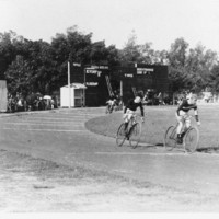 Image: cycle racing at Adelaide Oval. Two men on bicycles vie for the lead on a tarmac track.