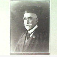 Image: black and white head shot of man wearing mortar board
