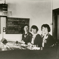"""Image: Three women are seated at a switchboard. Behind them is a sign that says """"Emergency Calls"""" and lists numbers for police, fire, ambulance, hospital and waterworks"""