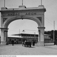 Image: Stone archway and buildings with dirt road in front