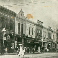 Image: a woman in a white dress crosses a road to join a large number of other pedestrians walking on the footpath. The road is lined with two storey terraced shops. A policeman stands under a street light to the left of the image.