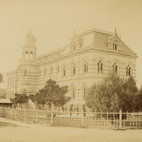 Image: Yellow-toned photograph of a large building with a turret